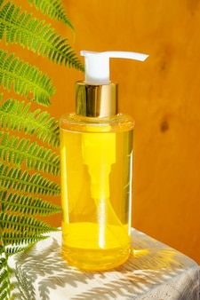 Butelka kosmetyczna z naturalnym olejkiem eterycznym na żółtym drewnianym pudełku. w pobliżu - liście paproci. pojęcie esencji organicznych, naturalnych produktów kosmetycznych i zdrowotnych. nowoczesna apteka.