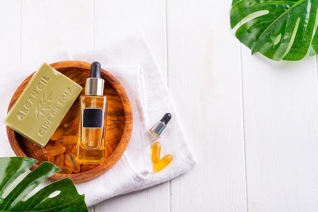 Butelka kosmetyczna z serum lub kwasem hialuronowym i mydłem z oliwek, kapsułki żelowe omega 3 na białym ręczniku drewnianym talerzu
