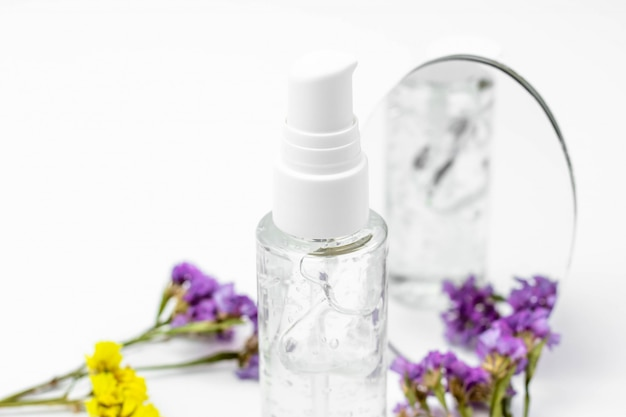 Butelka kosmetyczna z serum, żelem, kremem do twarzy na białym tle z kwiatami. kosmetyki do skóry, minimalizm