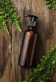 Butelka kosmetyczna ze szkła bursztynowego z zielonymi liśćmi na tle drewna. naturalna koncepcja. leżał na płasko, widok z góry.