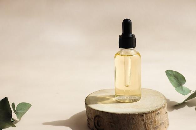 Butelka kosmetycznego olejku eterycznego na zbliżenie wycięte w drewnie z głębokimi cieniami