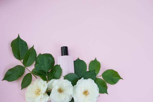 Butelka kosmetyków kobiecych z białymi kwiatami na różowo