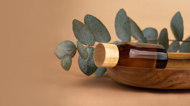 Butelka kosmetyków z brązowego szkła na drewnianej płycie z gałęzi eukaliptusa za. pastelowe tło z gałęzi świeżego eukaliptusa. koncepcja makieta organiczna, duży baner.