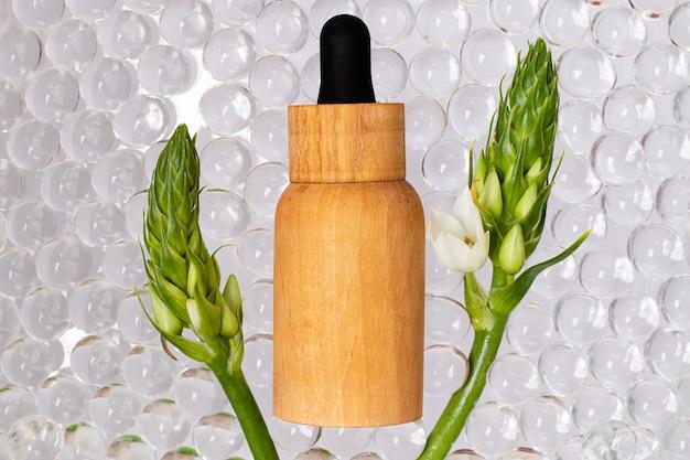 Butelka kosmetyków z naturalnego drewna, widok z góry. przezroczyste kulki hydrożelowe wokół nich. koncepcja organiczna.