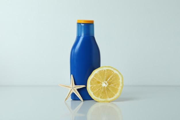 Butelka kremu do opalania, cytryny i rozgwiazdy na na białym tle