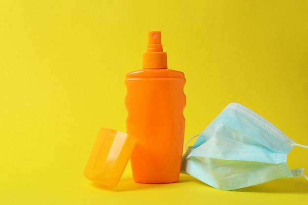 Butelka kremu do opalania i maski medycznej na żółtym tle na białym tle