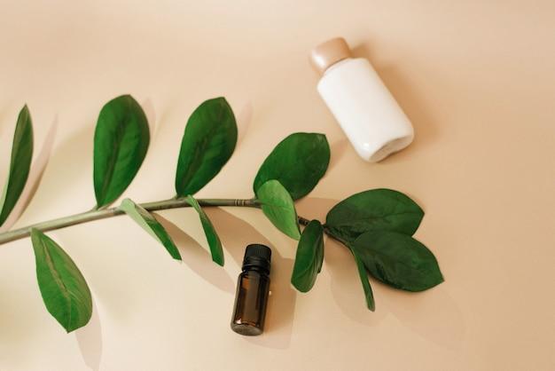 Butelka kremu do pielęgnacji skóry twarzy, brązowa szklana butelka z olejem i liśćmi zamiokulkas