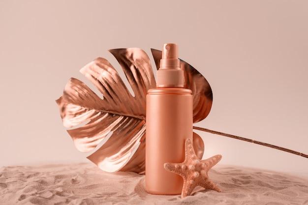 Butelka kremu lub balsamu z filtrem przeciwsłonecznym z tropikalnym liściem monstery w kolorze różowego złota. opieki zdrowotnej podczas wakacji koncepcji.