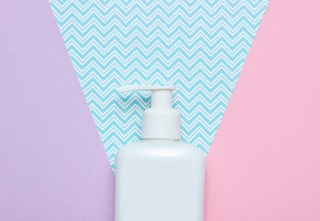 Butelka kremu na stole z papieru pastelowego. widok z góry