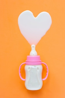 Butelka mleka dla dziecka na pomarańczowo.