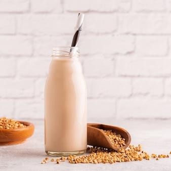 Butelka mleka gryczanego i surowej gryki na jasnym tle.