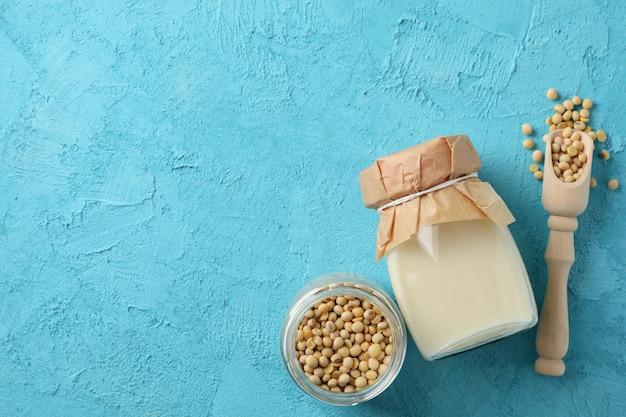 Butelka mleka sojowego, nasiona soi, szufelka na niebieskim stole. widok z góry