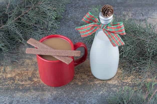 Butelka mleka z kokardą i szkła na marmurowym tle. zdjęcie wysokiej jakości