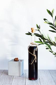 Butelka mocnego napoju alkoholowego z zieloną gałązką oliwną na jasnym tle