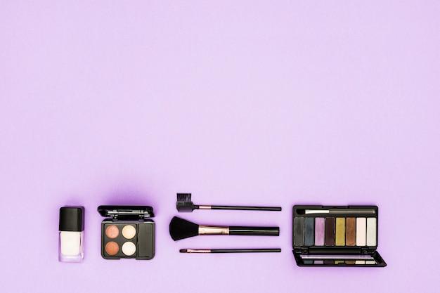 Butelka na podkład; paleta cieni do powiek i pędzle do makijażu na fioletowym tle