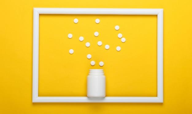 Butelka na tabletki na żółtej powierzchni z białą ramką