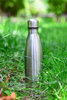 Butelka na wodę stalowa termofor wielokrotnego użytku na zielonej trawie pionowe zdjęcie