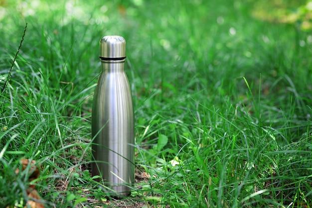 Butelka na wodę stalowa termofor wielokrotnego użytku na zielonej trawie