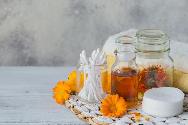 Butelka nalewki lub naparu z nagietka lekarskiego ze świeżymi kwiatami nagietka i wacikiem i patyczkami na biało