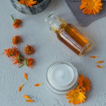 Butelka nalewki lub naparu z nagietka, maści, kremu lub balsamu ze świeżymi i suchymi kwiatami nagietka na jasnej powierzchni