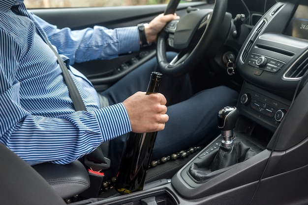 Butelka napoju alkoholowego w rękach kierowcy