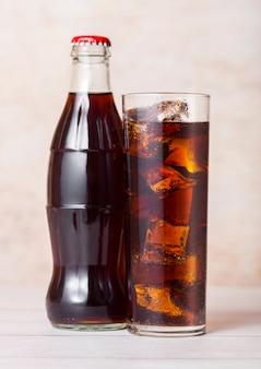 Butelka napoju gazowanego cola ze szklanką i kostkami lodu