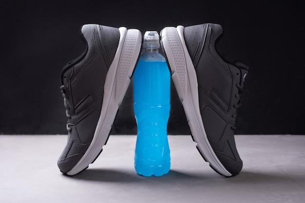 Butelka napoju izotonicznego i szare trampki na czarnym tle, woda z minerałami dla przywrócenia równowagi wodno-solnej po treningu, zbliżenie.