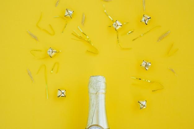 Butelka napoju między srebrnymi dzwonkami i błyskotką