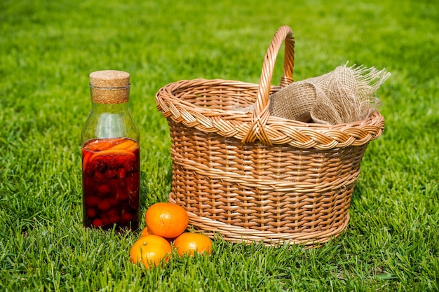 Butelka naturalnej domowej sody z jagodami i pomarańczami czysta ekologiczna żywność i napoje w stylu rustykalnym sok z pomarańczy i kosz na zielonej trawie