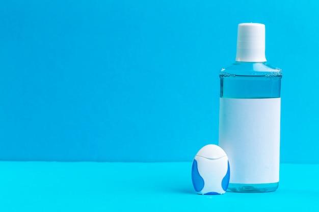 Butelka niebieskich płynów do płukania jamy ustnej.