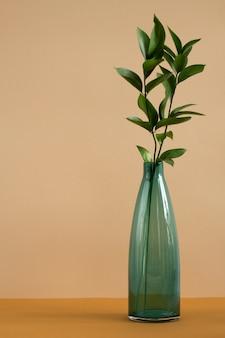 Butelka niebieskiego szkła z liśćmi świeżych zielonych roślin domowych stojących na stole na brązowej ścianie jako część wnętrza domu lub pracowni projektowania