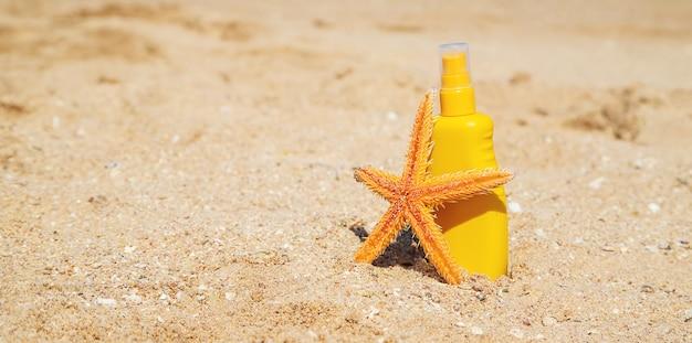 Butelka ochrony przeciwsłonecznej i rozgwiazda na plaży