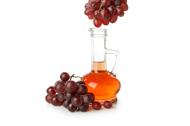 Butelka octu i winogron na białym tle