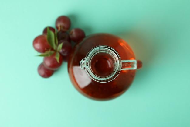 Butelka octu i winogron na miętowym tle