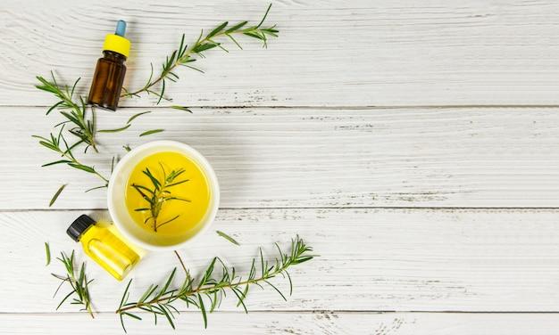 Butelka olejków eterycznych naturalne składniki spa olej rozmarynowy do aromaterapii i liści rozmarynu na tle drewna / kosmetyki organiczne z ekstraktami z ziół
