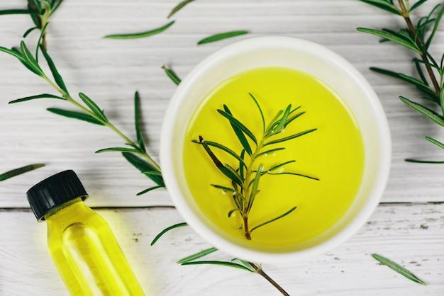 Butelka olejków eterycznych naturalne składniki spa olej rozmarynowy do aromaterapii i liści rozmarynu na tle drewna - kosmetyki organiczne z ekstraktami z ziół