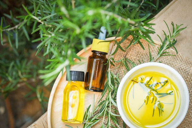 Butelka olejków eterycznych naturalne składniki spa olej rozmarynowy do aromaterapii i roślin liści rozmarynu na tle - kosmetyki organiczne z ekstraktami z ziół
