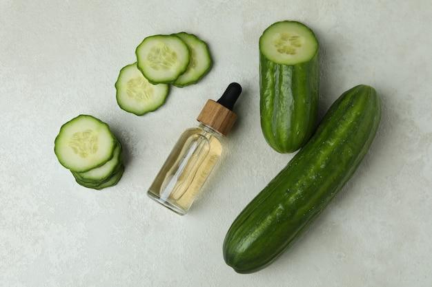 Butelka olejku kosmetycznego i ogórków na białej powierzchni teksturowanej