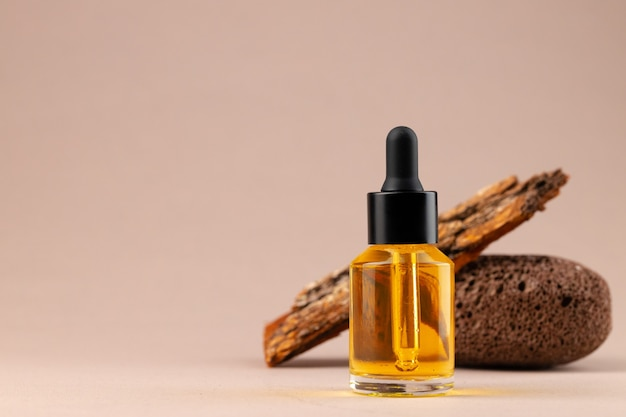Butelka olejku kosmetycznego z pipetą na beżowej powierzchni