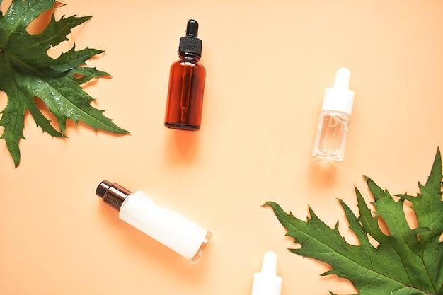 Butelka olejku, liście ziół leczniczych na różowym tle