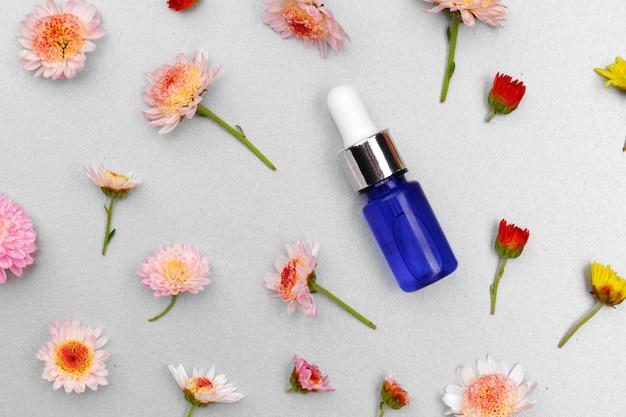 Butelka oleju kosmetycznego na tle kwiatów pąków płaskich leżał