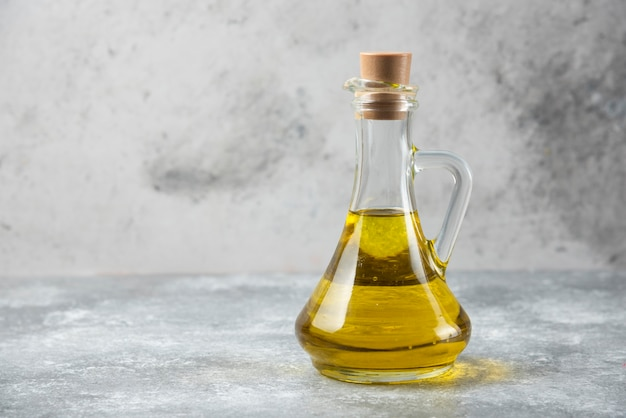 Butelka oliwy z oliwek na marmurowym stole.