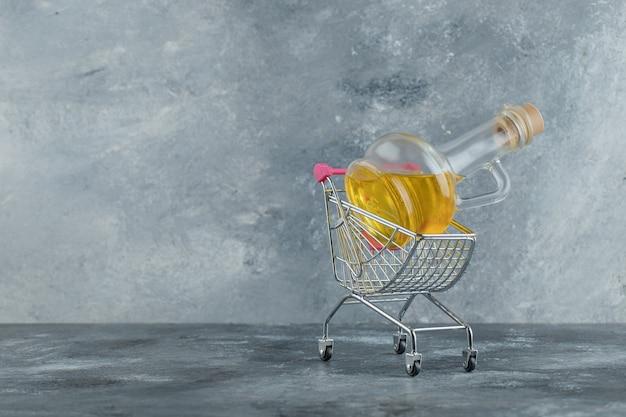 Butelka oliwy z oliwek w metalowym wózku