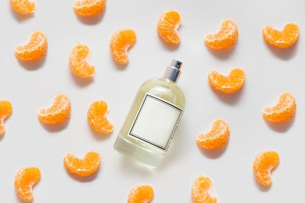 Butelka pachnącego oleju lub perfum na białej ścianie ozdobiona plasterkami mandarynki. koncepcja cytrusowych perfum lub aromaterapii, owocowe aromaty.