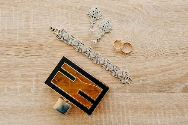 Butelka perfum bransoletka kolczyki i obrączki na jasnej drewnianej powierzchni