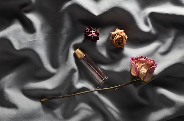 Butelka perfum i pąków suszonych róż na szarym jedwabiu. romantyczny wygląd. widok z góry.
