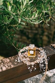 Butelka perfum i złote obrączki pary młodej na drewnianej poręczy w wieńcu
