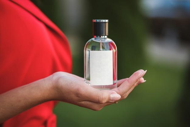 Butelka perfum kobiecej dłoni. młoda stylowa kobieta trzyma butelkę perfum. modne perfumy w rękach kobiet. dziewczyna rozpylania perfum. piękne kobiece dłonie. perfumy dla kobiet