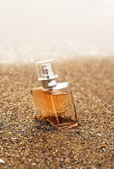 Butelka perfum na piasku nad morzem. żółty piasek na plaży, fale, morskie kosmetyki.