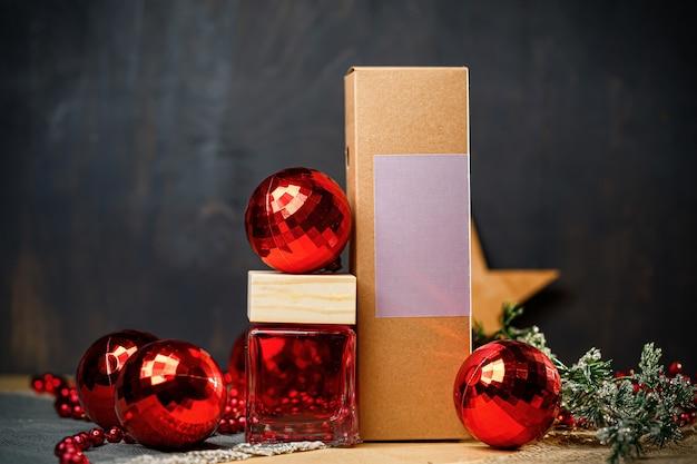 Butelka perfum na prezent noworoczny. stylowa noworoczna butelka perfum znajduje się pod drzewem. modne perfumy w noworocznych lokalizacjach. perfumy dla kobiet